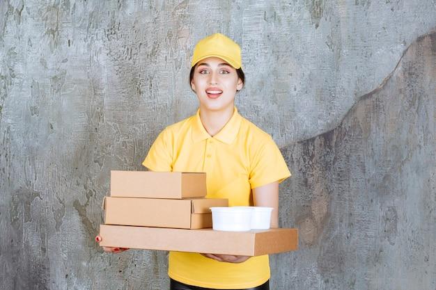 Correio feminino em uniforme amarelo, entregando várias caixas de papelão e copos para viagem.