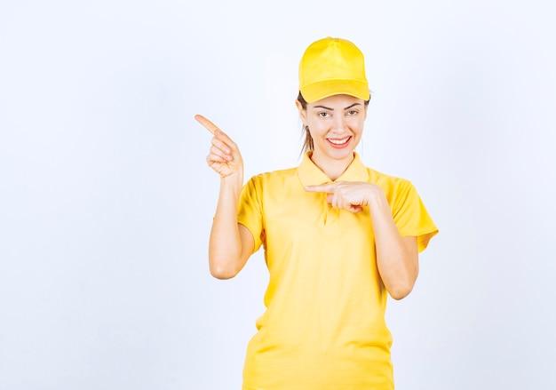 Correio feminino em uniforme amarelo, mostrando algo à esquerda.