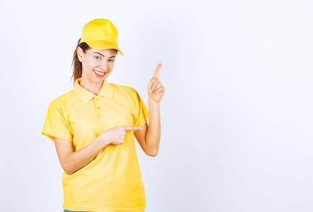 Correio feminino em uniforme amarelo, mostrando algo acima.