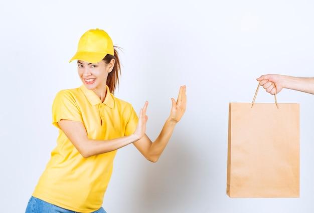 Correio feminino em uniforme amarelo, recusando-se a receber uma caixa de compras de papelão.
