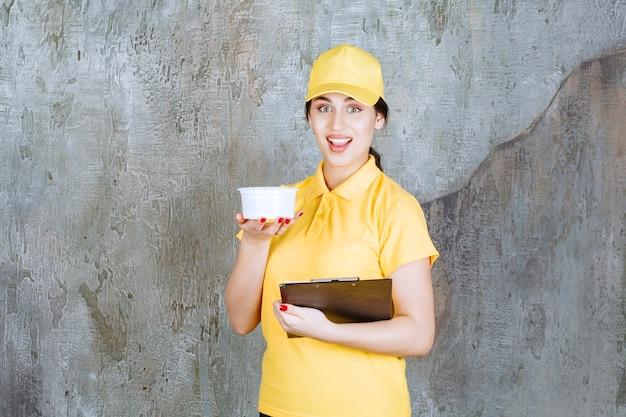 Correio feminino em uniforme amarelo, segurando um copo para viagem e uma pasta preta.