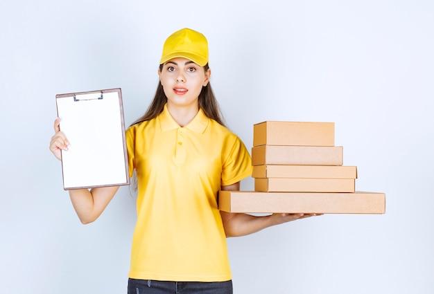 Correio feminino em uniforme amarelo segurando um monte de caixas de papelão e a área de transferência sobre a parede branca.