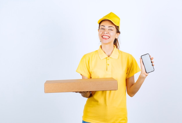 Correio feminino em uniforme amarelo segurando um pacote de papelão e mostrando seu smartphone branco.