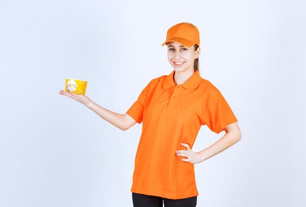 Correio feminino em uniforme amarelo segurando uma xícara de macarrão para viagem.