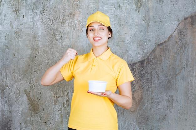 Correio feminino em uniforme amarelo, segurando uma xícara para viagem e apreciando o produto.