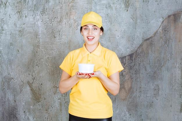 Correio feminino em uniforme amarelo, segurando uma xícara para viagem.