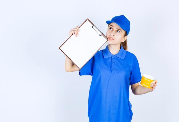Correio feminino em uniforme azul segurando um copo de macarrão para viagem e apresentando a lista de assinaturas ao cliente.