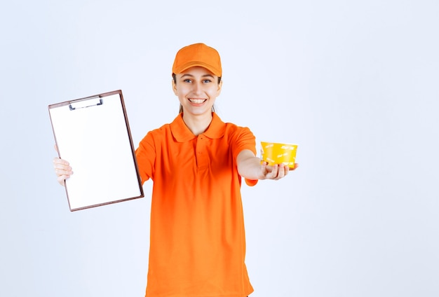Correio feminino em uniforme laranja, segurando uma xícara de macarrão amarelo e pedindo uma assinatura.