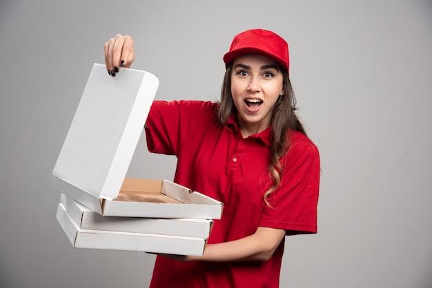 Correio feminino em uniforme vermelho, segurando a caixa de pizza empy na parede cinza.
