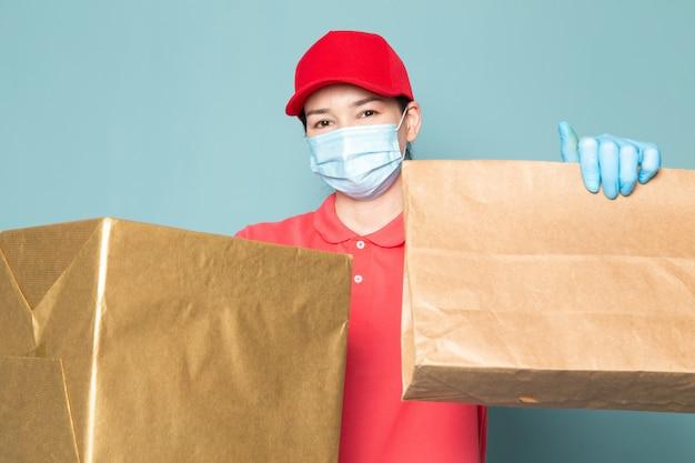 Correio feminino jovem em t-shirt rosa boné vermelho máscara azul estéril azul luvas segurando a caixa na parede azul