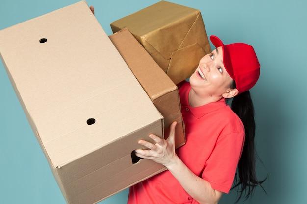 Correio feminino jovem na tampa de camiseta rosa vermelha segurando a caixa na parede azul