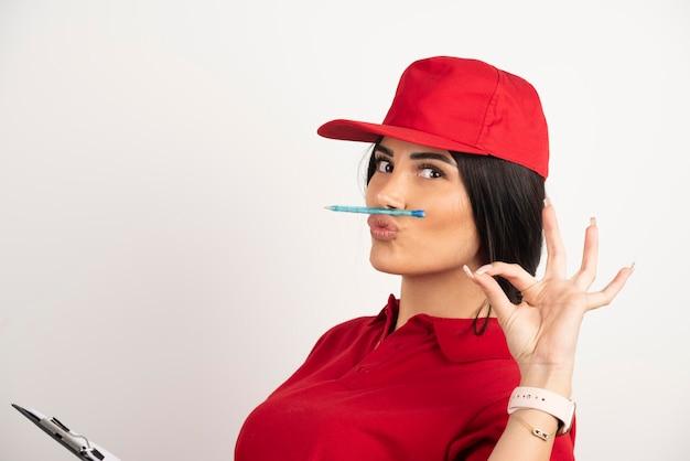 Correio feminino segurando a caneta na boca e mostrando sinal de ok. foto de alta qualidade