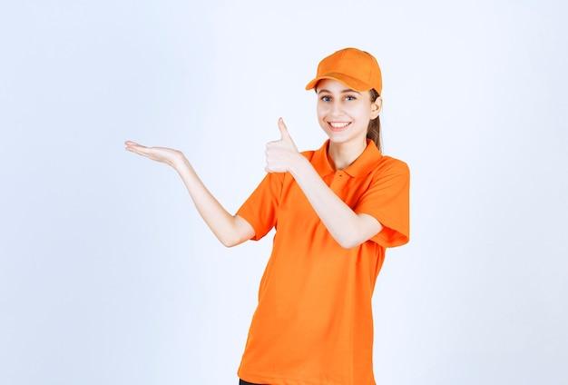 Correio feminino vestindo uniforme laranja e boné aparecendo o polegar.