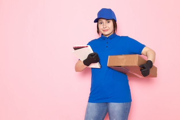 Correio jovem em jeans azul boné azul polo segurando o caderno pacote rosa
