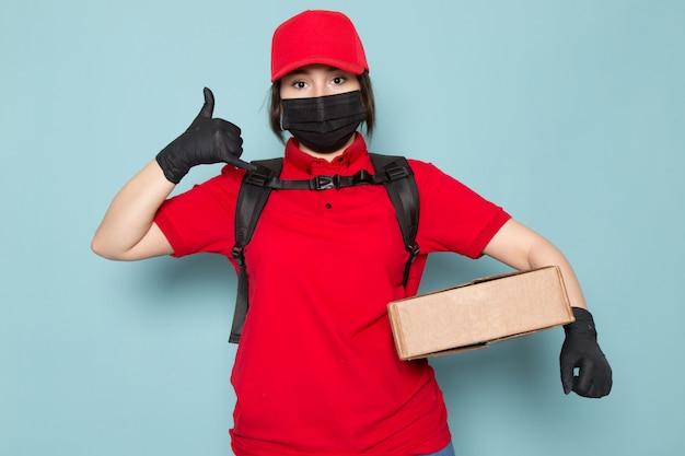 Correio jovem no polo vermelho tampa vermelha máscara protetora estéril preta mochila preta segurando o pacote azul