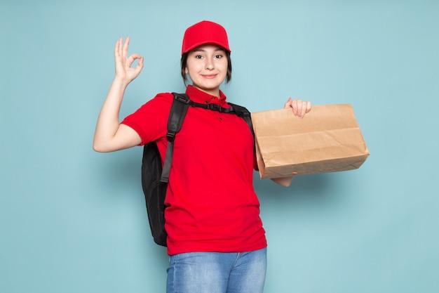 Correio jovem polo vermelho boné preto mochila preta segurando pacote sorrindo no azul