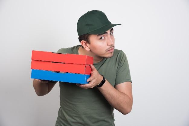 Correio jovem segurando três caixas de pizza em fundo branco.