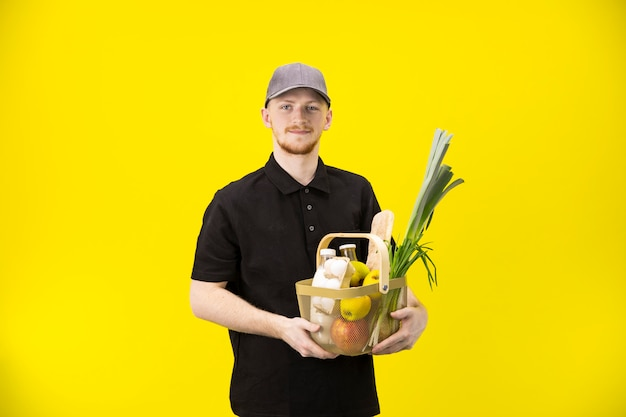 Correio mantém cesta com mantimentos isolados na parede amarela, copie o espaço