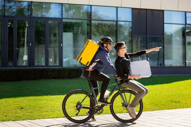 Correio masculino com bolsa térmica está carregando um cara com uma caixa no porta-malas de uma bicicleta.
