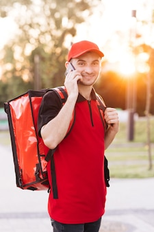 Correio masculino com caixa isotérmica de comida em scooter elétrico chega à entrada da casa