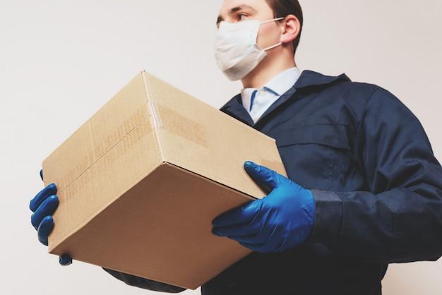 Correio masculino com uma caixa em uma máscara protetora e luvas. entrega em domicílio de alimentos e medicamentos durante uma pandemia de covid-19.