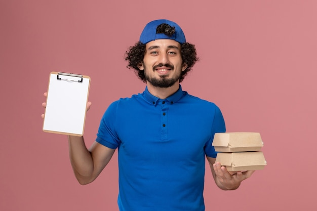 Correio masculino de frente para o uniforme azul e capa segurando pacotes de comida com bloco de notas na parede rosa. serviço de entrega de uniforme