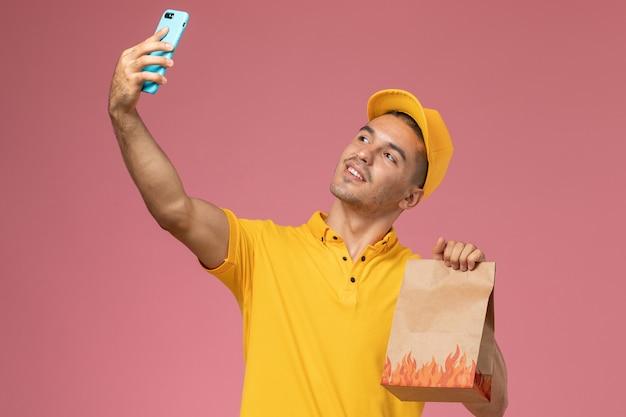 Correio masculino de uniforme amarelo tirando uma selfie com o pacote de comida na mesa rosa