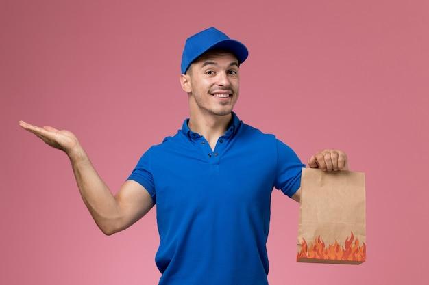 Correio masculino de uniforme azul segurando um pacote de comida de papel sorrindo na parede rosa, entrega de serviço de uniforme de trabalhador de vista frontal