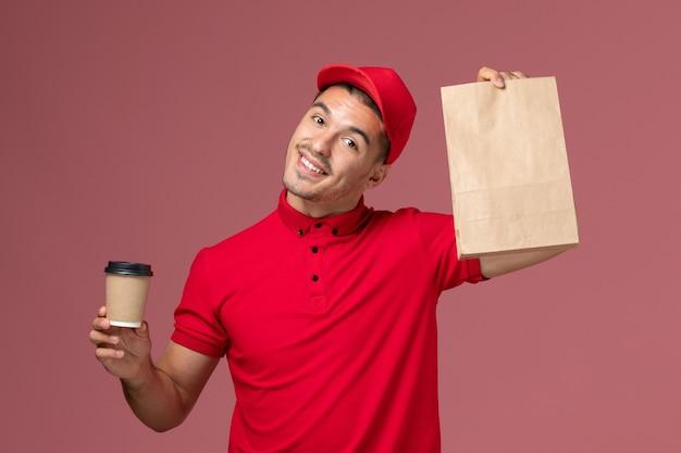 Correio masculino de uniforme vermelho segurando uma xícara de café de entrega e um pacote de comida na parede rosa serviço de entrega de uniforme de trabalho
