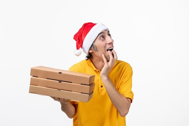 Correio masculino de vista frontal com caixas de pizza em serviço de uniforme de serviço de parede branca