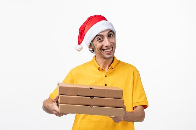 Correio masculino de vista frontal com caixas de pizza em trabalho de serviço de entrega uniforme de parede branca