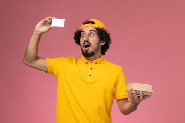 Correio masculino de vista frontal em uniforme amarelo e capa com cartão e pequeno pacote de entrega de comida nas mãos sobre o fundo rosa claro.