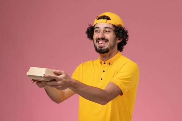 Correio masculino de vista frontal em uniforme amarelo e capa com pouco pacote de comida de entrega nas mãos sobre o fundo rosa.