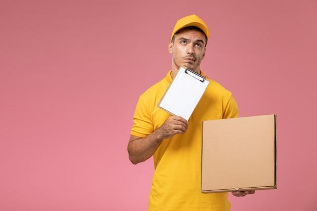 Correio masculino de vista frontal em uniforme amarelo pensando e segurando o bloco de notas junto com a caixa de entrega de comida na mesa rosa