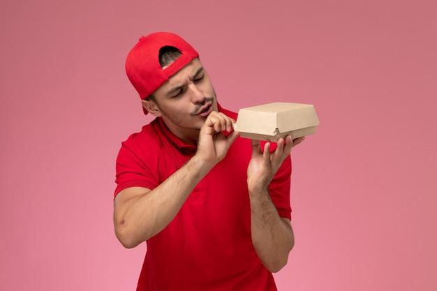 Correio masculino de vista frontal em uniforme vermelho e capa segurando o pequeno pacote de entrega no fundo rosa.
