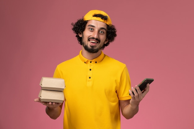 Correio masculino de vista frontal na capa uniforme amarela com pacotes de telefone e comida nas mãos sobre fundo rosa claro.