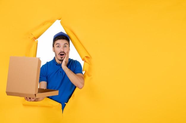 Correio masculino de vista frontal segurando uma caixa de pizza aberta no espaço amarelo