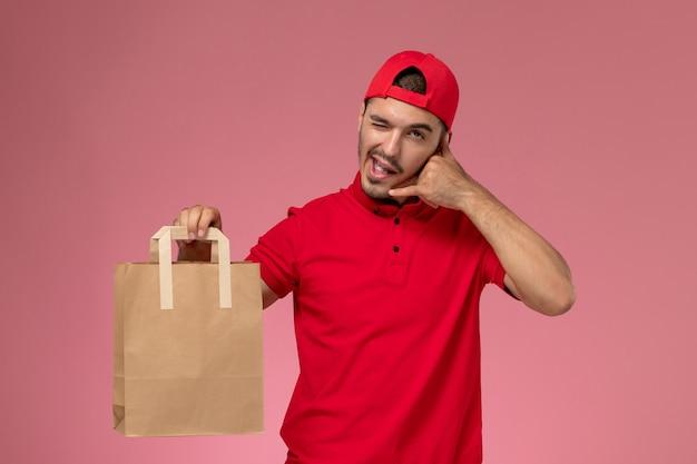 Correio masculino jovem de vista frontal na capa uniforme vermelha, segurando o pacote de comida de papel no fundo rosa claro.