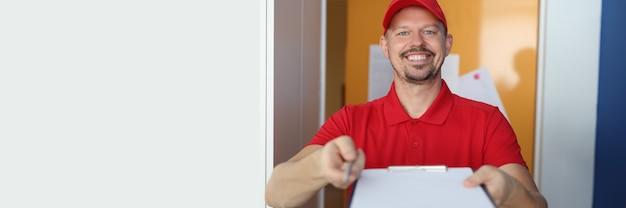 Correio masculino sorridente oferece uma prancheta e uma caneta.