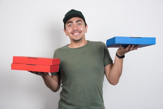 Correio positivo carregando três caixas de pizza em fundo branco.