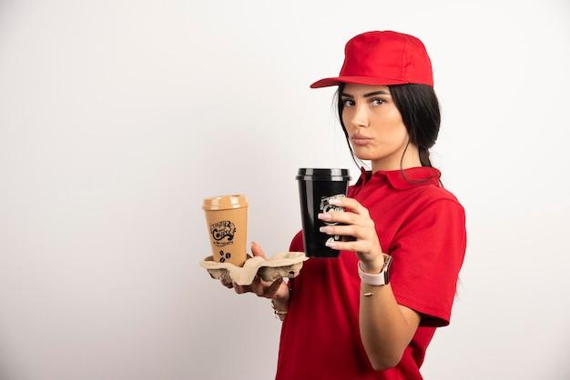 Correio sério posando com duas xícaras de café no fundo branco. foto de alta qualidade