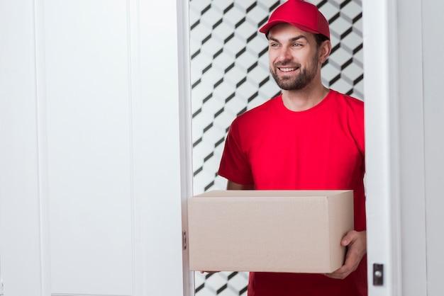 Correio sorridente segurando uma caixa pesada