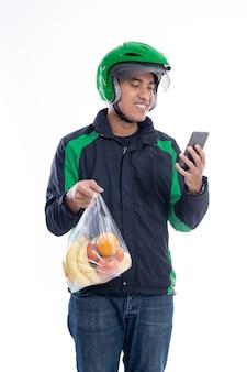 Correio usando capacete e jaqueta uniforme segurando comida isolada
