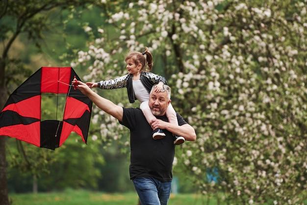 Correndo com a pipa vermelha. criança sentada nos ombros do homem. se divertindo