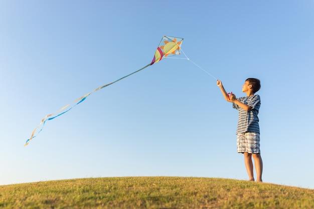 Correndo com pipa nas férias de verão, prado perfeito e céu à beira-mar