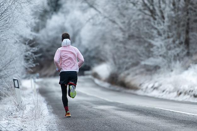 Correndo durante o treinamento na estrada gelada no inverno