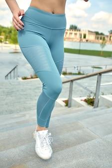 Correndo na cidade esporte motivação jovem mulher correndo lá em cima nas escadas da cidade.