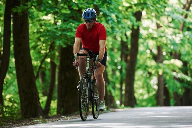 Correndo para frente. ciclista de bicicleta está na estrada de asfalto na floresta em um dia ensolarado