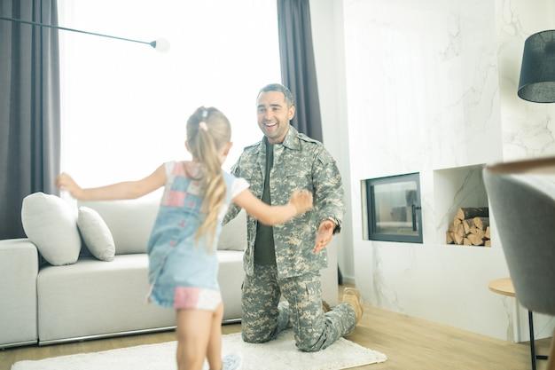 Correndo para o pai. filha loira correndo para o pai voltando para casa após o serviço militar