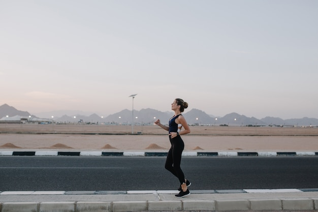 Correndo, treino na estrada no início da manhã de mulher bonita alegre. treinamento de forte desportista, energia, motivação, estilo de vida saudável, bom humor.